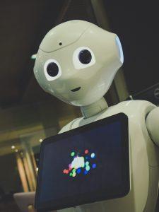 white robot toy holding black tablet